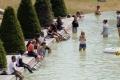 بالصور.. سائحون يواجهون الحرَّ الشديد في فرنسا بالاستحمام في نافورة بالقرب من برج إيفل